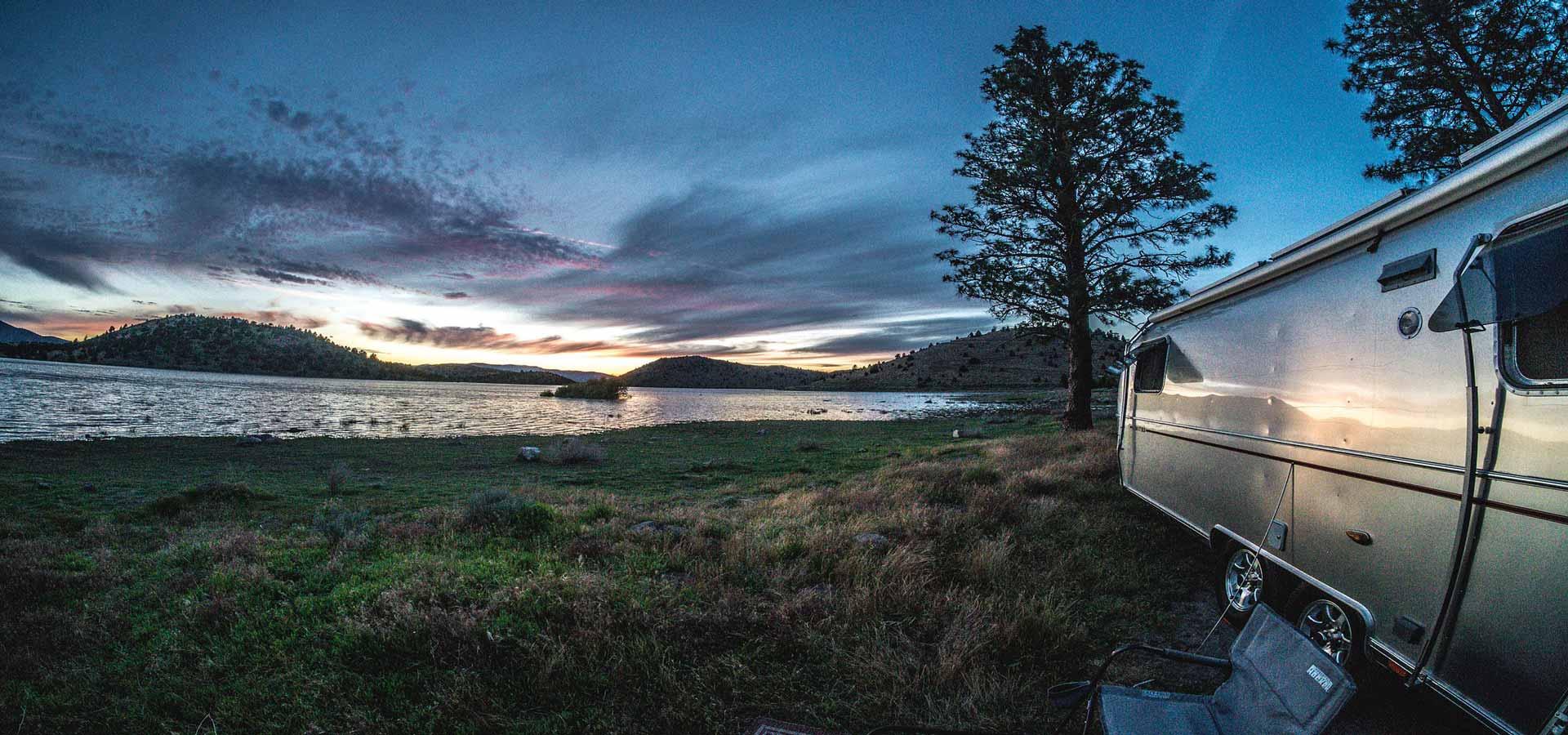 Camper am Seeufer im Sonnenuntergang